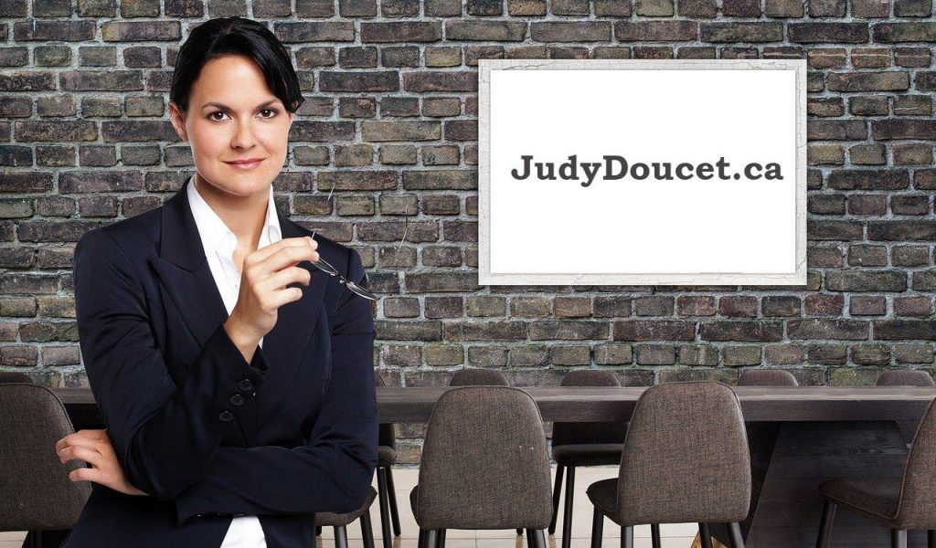 Woman standing in front of white board with caption JudyDoucet.ca