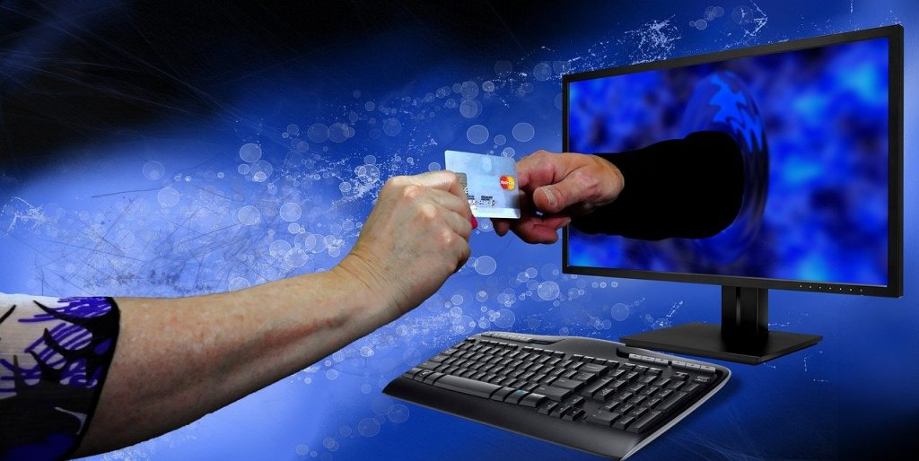 Image of two hands passing through computer with caption Shop Virtually From Anywhere